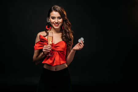 smiling beautiful brown haired girl in red corset holding glass of champagne and casino chips isolated on black Stock Photo - 116321247
