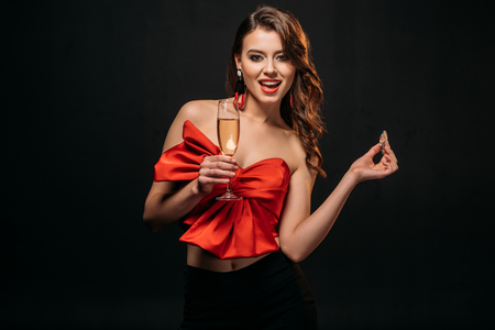 excited brown haired girl in red corset holding glass of champagne and casino chips isolated on black
