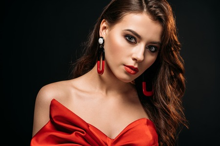 portrait of beautiful brown haired girl in red corset and earrings looking at camera isolated on black