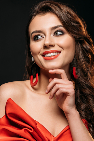 portrait of smiling beautiful brown haired girl in red corset and earrings looking away isolated on black