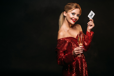 happy attractive girl in red shiny dress holding joker card and glass of champagne isolated on black, looking at camera Stock Photo