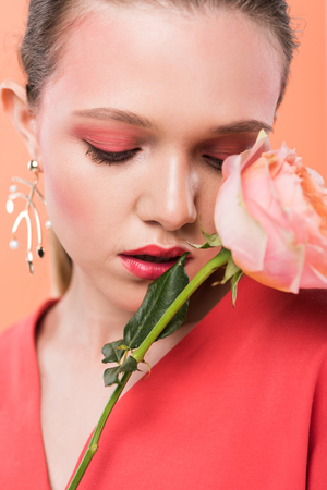 portrait of beautiful stylish girl holding rose and posing isolated on living coral Stok Fotoğraf