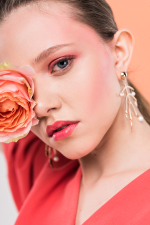 selective focus of beautiful stylish girl holding rose and posing with living coral on background