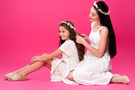 happy young mother plaiting braid to beautiful smiling daughter on pink