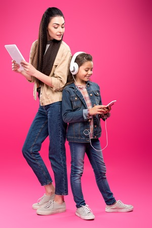 full length view of smiling mother holding digital tablet and looking at daughter in headphones using smartphone on pink