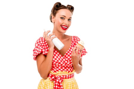 Smiling pin up girl holding cupcake and bottle with whipped cream isolated on white 스톡 콘텐츠