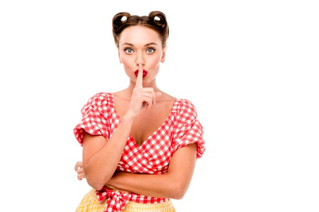 Pin up girl in retro clothes showing silence sign isolated on white
