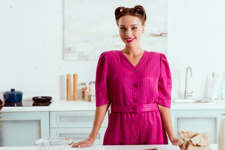 beautiful smiling pin up girl standing by kitchen table