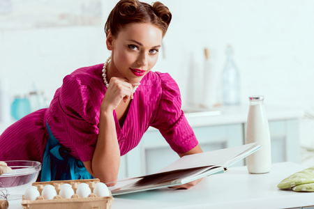 Pretty pin up girl reading recipes book while leaning on kitchen table Stock Photo
