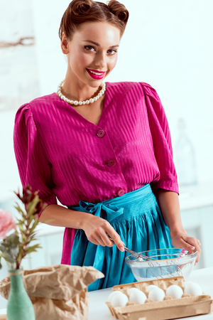 Pretty pin up girl mixing pastry ingredients standing by kitchen table and looking at camera Imagens