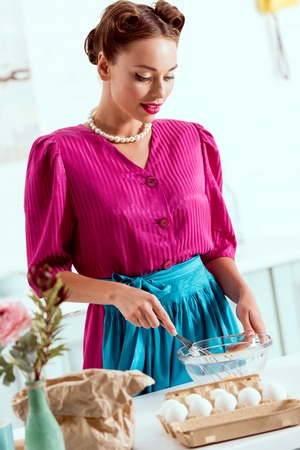 Beautiful pin up girl mixing pastry ingredients in glass bowl Stock Photo