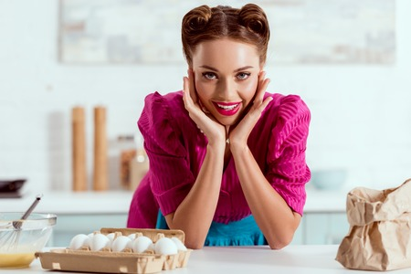 Pretty pin up girl leaning up on kitchen table with different products and looking at camera Stock Photo