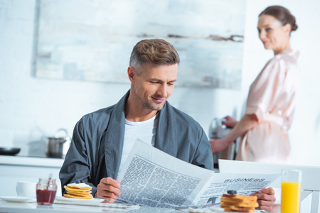 man reading newspaper during breakfast while woman cooking on background Фото со стока