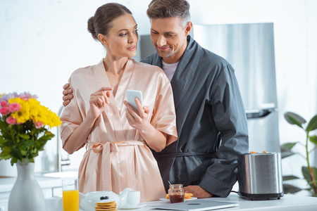 beautiful adult couple in robes using smartphone during breakfast in kitchen