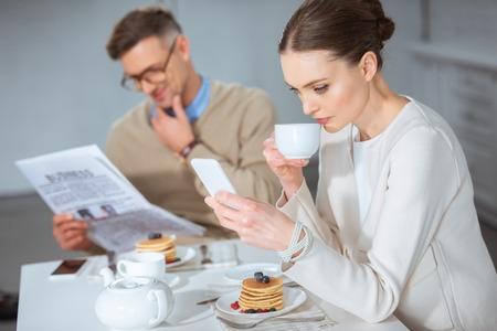 adult couple reading newspaper, drinking tea and ignoring each other during breakfast in morning