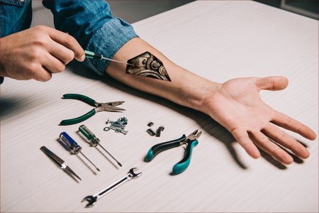 cropped view of man repairing metallic mechanism in arm with wrench and pliers Stok Fotoğraf
