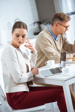 woman talking on smartphone and ignoring man during breakfast in morning