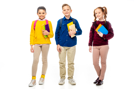 schoolchildren with backpacks and multicolored books looking at camera isolated on white