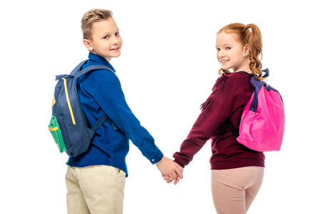 schoolkids holding hands and smiling at camera isolated on white 스톡 콘텐츠