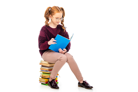 adorable schoolgirl in glasses reading book isolated on white