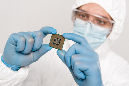 selective focus of microchip in hands of scientist wearing latex gloves isolated on grey