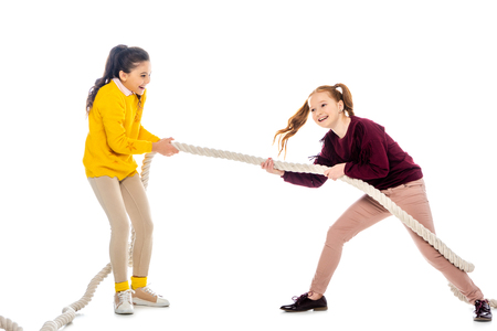 two happy schoolgirls laughing and pulling rope isolated on white