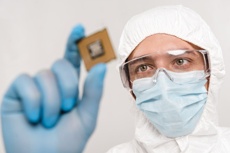 selective focus of scientist looking at microchip in latex glove isolated on grey