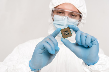 selective focus of microchip in hands of scientist wearing latex gloves and googles isolated on grey Imagens