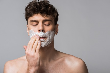 handsome man applying shaving foam on face, isolated on grey