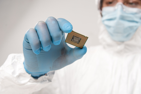 selective focus of microchip in hand of scientist wearing latex glove on grey background 写真素材