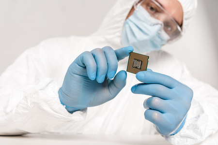 selective focus of microprocessor in hands of scientist in googles on grey background