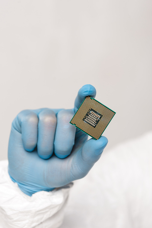 cropped view of microchip in hand of scientist isolated on grey