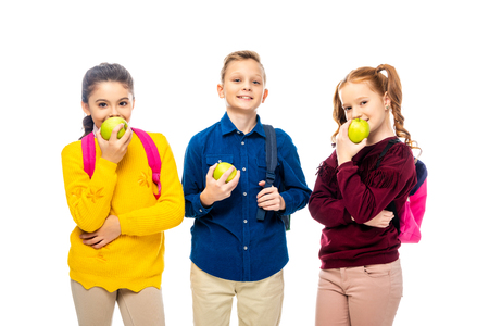 cute schoolchildren with backpacks eating apples and looking at camera isolated on white