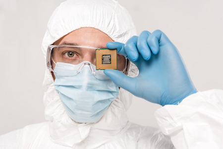 scientist in googles holding microchip in hand isolated on grey