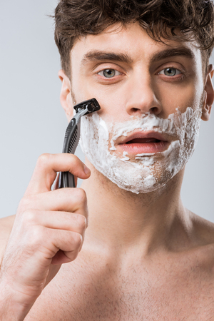 young man foam on face shaving with razor, isolated on grey Фото со стока