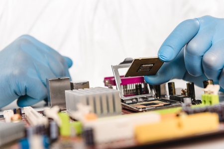 cropped view of microchip in hands of scientist in latex gloves