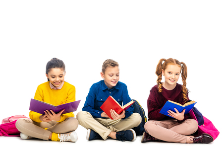 smiling schoolchildren sitting and reading books with multicolored covers isolated on white