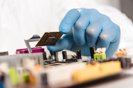 cropped view of microchip in hand of male scientist near motherboard
