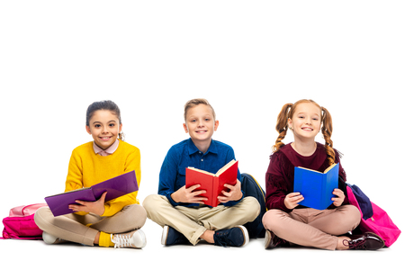 cheerful schoolchildren sitting, holding books and looking at camera isolated on white