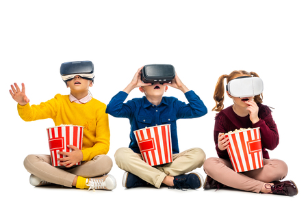 amazed children with virtual reality headsets on heads holding striped buckets and eating popcorn isolated on white