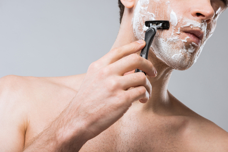 cropped view of man foam on face shaving with razor, isolated on grey