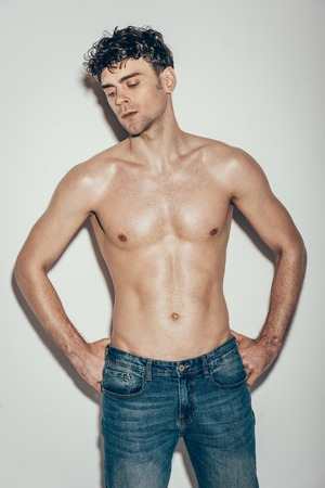 sexy stylish muscular macho in jeans posing on grey