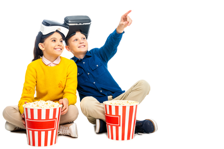smiling boy with virtual reality headsets on head pointing with finger and cute schoolgirl holding striped popcorn bucket isolated on white Фото со стока - 116299115