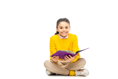 cheerful schoolgirl holding purple book and looking at camera isolated on white