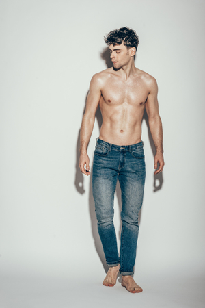 shirtless muscular macho in jeans posing on grey