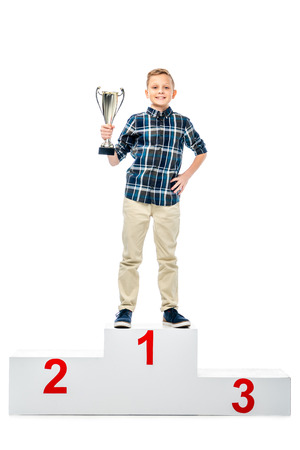 happy boy standing on winner podium, holding trophy cup, smiling and looking at camera isolated on white
