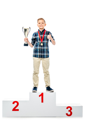 smiling boy standing on winner pedestal, holding trophy cup, showing thumb up and looking at camera isolated on white 免版税图像