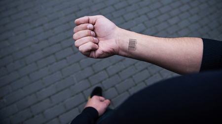cropped view of barcode on male hand  with bricks on background Stok Fotoğraf