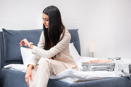 beautiful young woman in stylish white suit sitting on bed with suitcase and checking wristwatch Stock Photo
