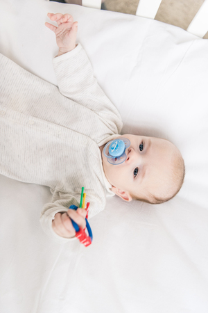 overhead view of little baby with pacifier holding toy while lying in crib